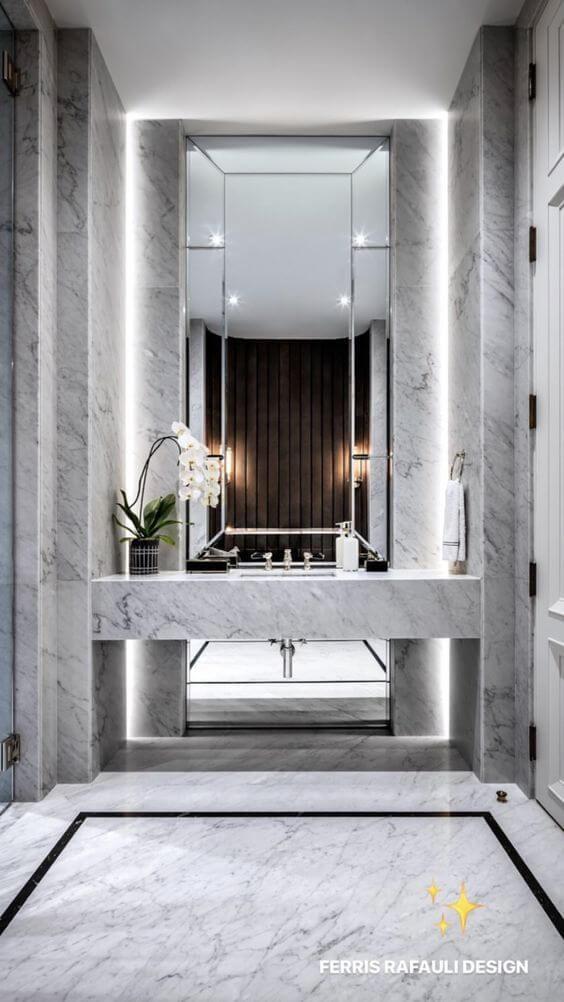 洗面台と壁面が同じ素材にしてあることで一体感があります。間接照明がありラグジュアリー感を醸し出しています。