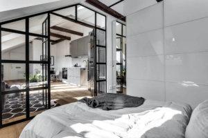 床が古材で建具がブラックの海外インテリア ベッドルーム側からリビングを見たインテリアイメージ。白いシーツでメイキングされていて清潔感があります。