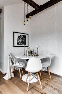 床が古材で建具がブラックで白いシェルチェアーと丸いテーブルでコーディネートされた海外インテリア