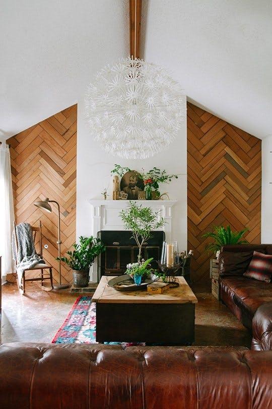 壁面の一部を木材を貼りヘリンボーンを採用しています。ソファーはダークブラウンレザーでかなり使い込まれたものを使用しています。観葉植物を多めに置いています。