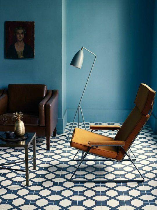 空間全体をブルーで統一してリビングチェアがからし色を使用しています。ブルーの模様のある床は、このリビングルームではレトロで静かな雰囲気を作り出します。