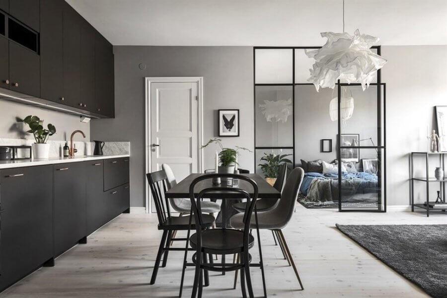 白い床にブラックのキッチンとダイニングテーブルです。かっこいい部屋ですね。ベッドメーキングでブルーを使っているのがポイントです。