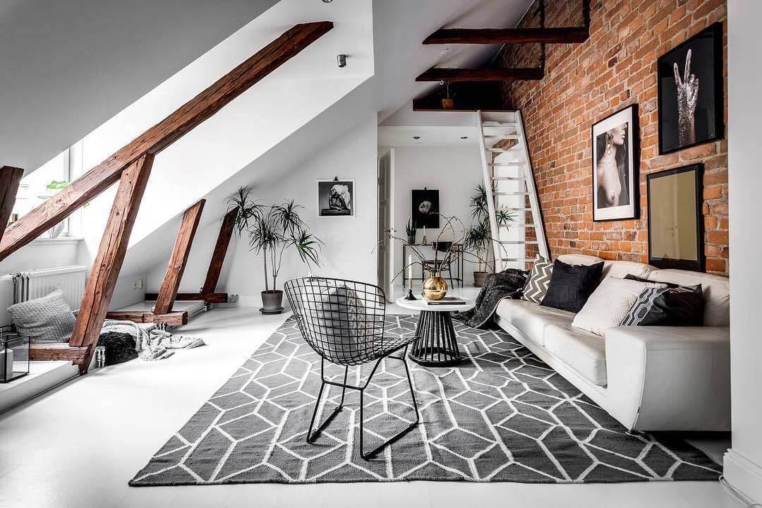 白い床と白いソファーとライトグレーの幾何学模様のラグマットでコーディネートしています。壁がレンガを使っていてとてもお洒落です。