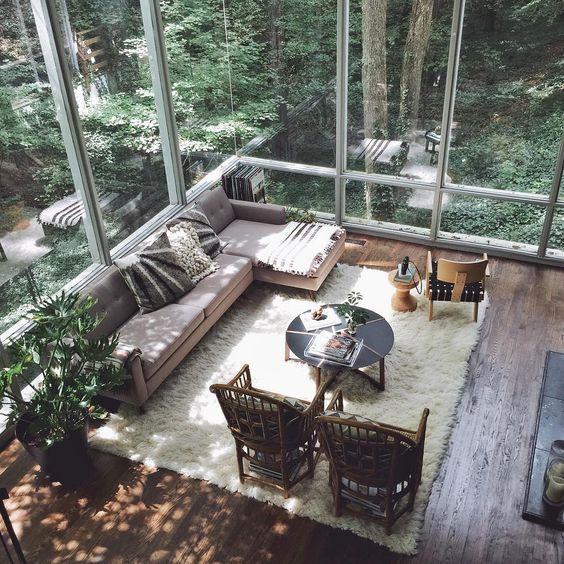 ガラス張りの空間で自然に囲まれています。景色のキレイな空間は基本的にシンプルなデザインの方が良いと思われます。フローリングの色はダークブラウンからからミディアムブラウンからの中間位といったところでしょうか。リビングテーブルはブラックの丸いテーブルを使用しています。リビングチェアは2脚並べています。リビングチェアを二台並べてソファーと絡ませる方法は海外インテリア事例ではよく見られるレイアウトです。