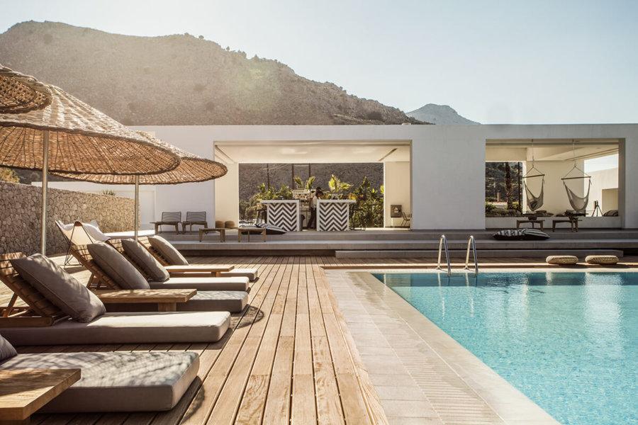 ギリシャのホテルCasa Cook Rhodesのプールサイドはタイルの敷詰めてウッドデッキを使用しています。