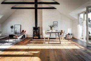 床が古材でソファが白、黒い暖炉あり海外のインテリア事例 暖炉があるリビング