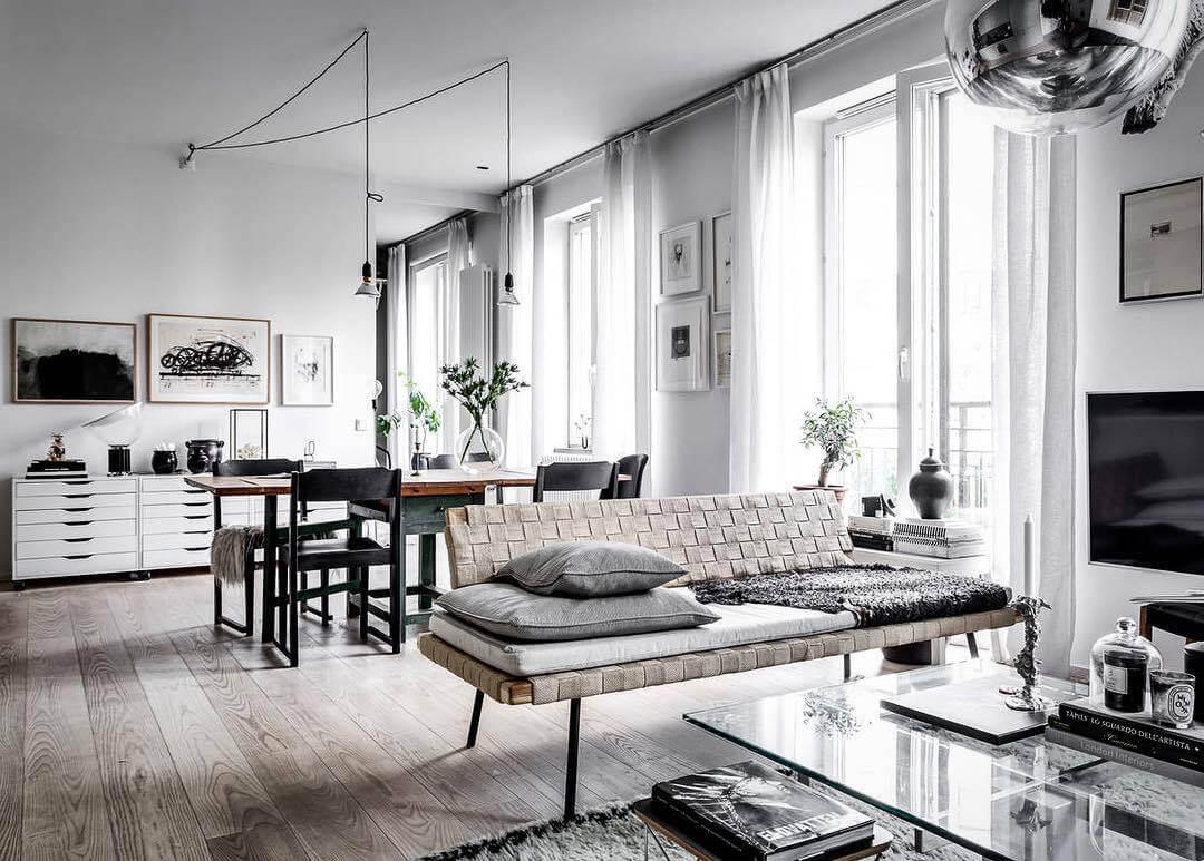 フローリングがライトグレーで壁が白色です。カーテンもホワイトで統一されています。リビングテーブルはガラステーブルです。グレーのクッションをソファーの上に積んでいます。