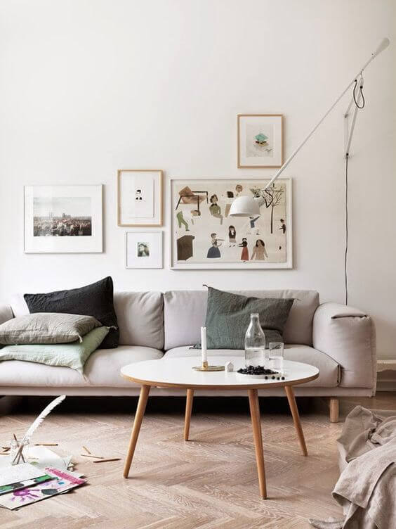 明るい色のヘリンボーンのフローリングにベージュ系のソファーをコーディネートしている海外インテリアのイメージ画像。クッションはグリーン系でグラデーションを使っている。絵の飾り方もランダムで飾っています。