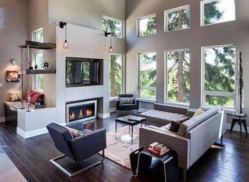 フローリングはダークブラウンカラーでソファーはライトグレーのコーナータイプを使用しています。暖炉が壁面に埋め込んでありその上にテレビが入りされています。リビングテーブルはかなりコンパクトな正方形のものを置いています。食事をするわけではないのでリビングテーブルは大きいものを求めていない人が多いのかもしれません。それよりもリビングチェアを置いてみんなで会話を楽しむことを重視しているようです。