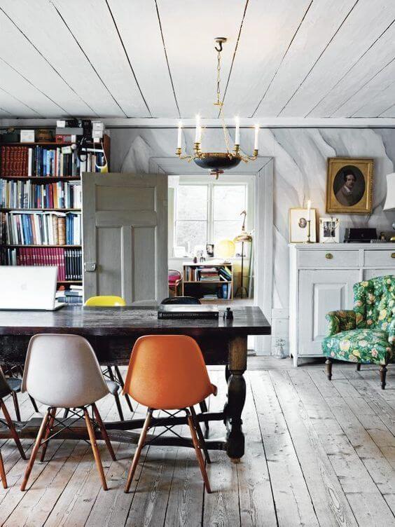 古材の床にオレンジのシェルチェアーを混ぜてお部屋に彩りを取り入れている。古い食卓テーブルも使い込まれていて味があります。