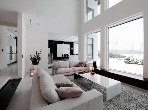 吹き抜けでかなり天井が高い空間です。白いタイルで白いソファーになっています。景色がすごく綺麗なのでそちらが見えるように配置しています。ブラックカラーを所々に使用しており空間を引き締める役割を担っています。
