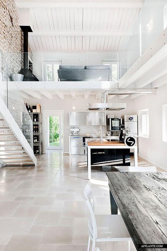 タイルの配列がまだらになっていて大きさも不規則です。キッチンはシルバーとホワイトを基調としていて吹き抜けになっているインテリアです。暖炉がにかいに配置されています。壁面が1面だけレンガを使っていてやや古い物件だと思われますがきれいにリフォームされています。