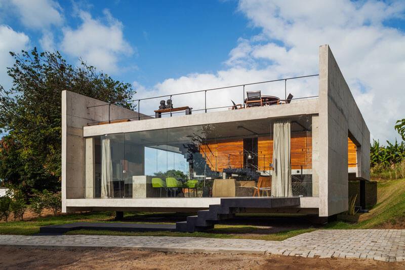 屋外生活空間を祝うことを意図したユニークな建築構造を持つ現代的なコンクリートの家があります。近代的なコンクリートの家は二つの別々の高い建物を持っているので、家の中央に空いている屋外スペースがあります。最初のフロントセメントは地形の地面からわずかに高くなっており、透明なオープンプランのリビング - ダイニング - キッチンのフロアプランで構成されています。第2のコンクリートブロック建物は、第1の建物の正面の高さが高く、寝室やバスルームのような私的空間を意図している。