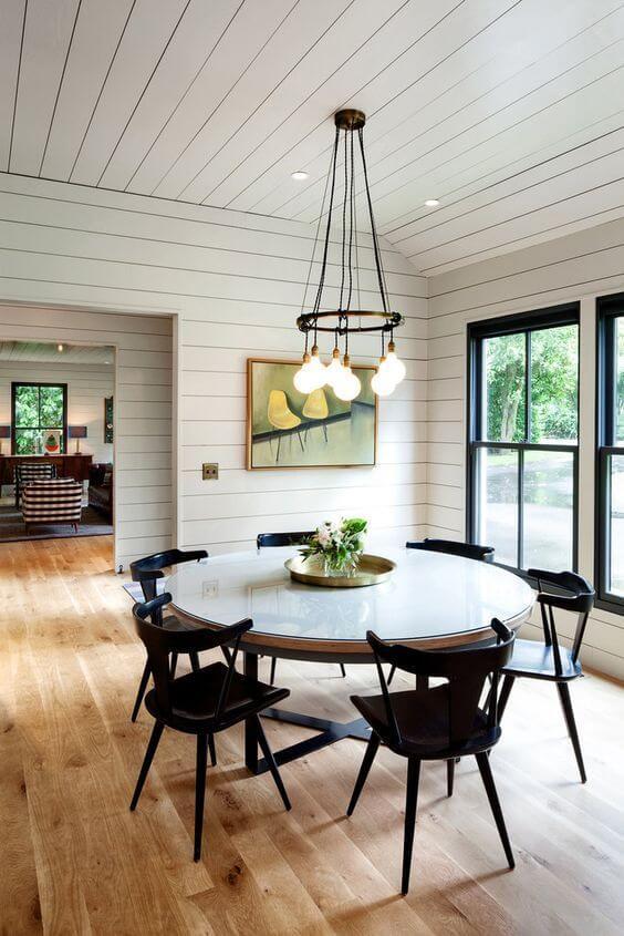 明るいフローリングで丸いテーブルにブラックの知恵合わせています。窓からの光もたくさん差し込み森に囲まれた家でものすごく空気が美味しそうです。時間がゆっくり流そうなダイニングですね。