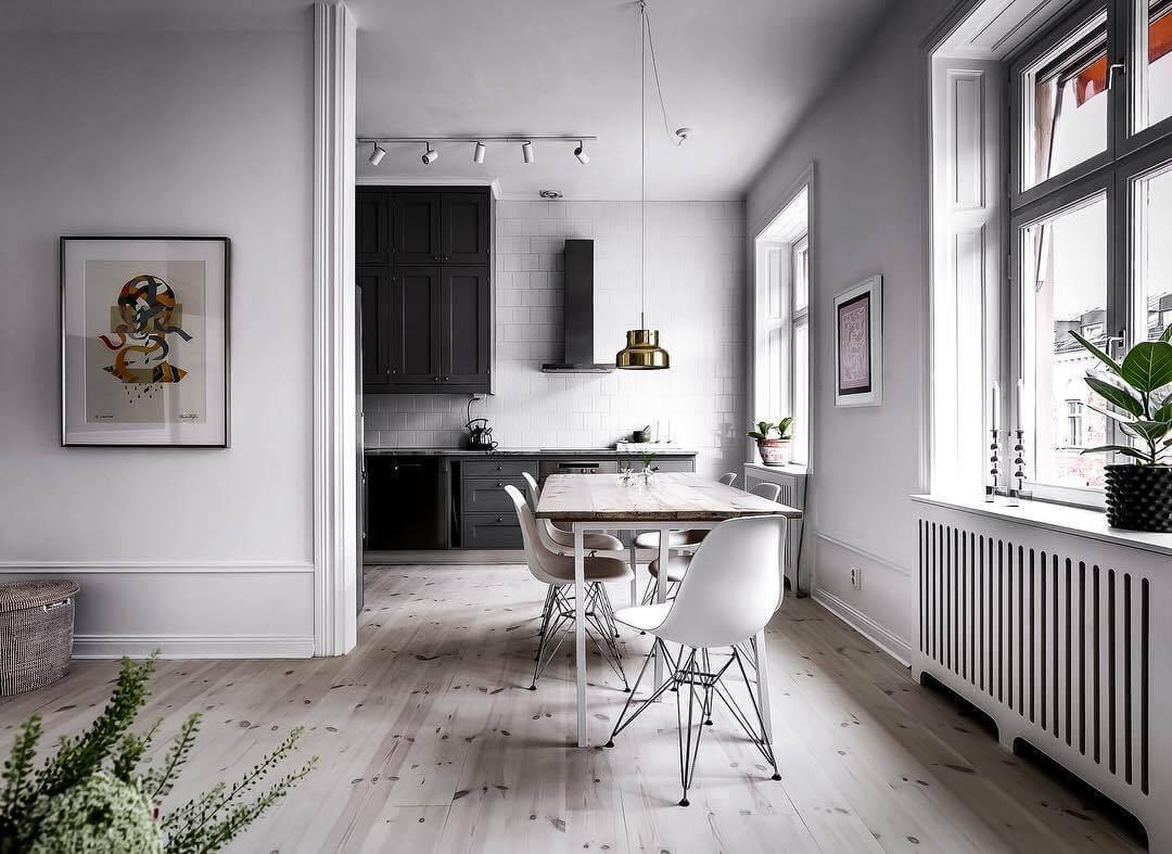 白い床と縁のあるフローリングと黒いキッチンがとてもお洒落です。