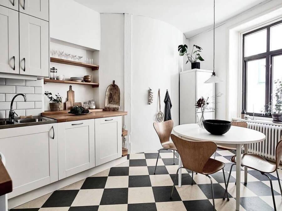白と黒のタイルの上にホワイトのダイニングテーブルと木目のセブンチェアがおしゃれな北欧風のインテリア。