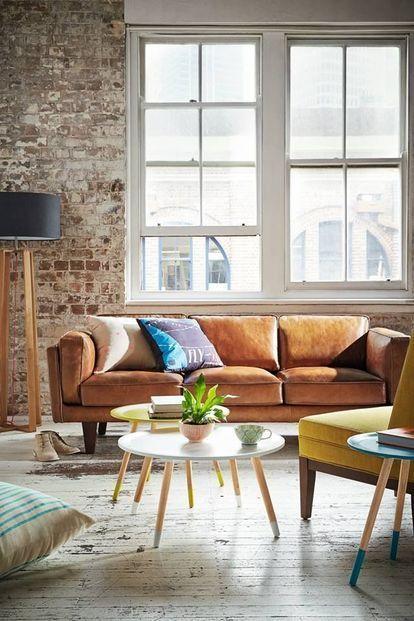 古い床と使い込まれたレンガの壁がレトロな雰囲気を醸し出しているアパートメント。リビングテーブルがポップな印象で色使いのギャップがおしゃれな一例。