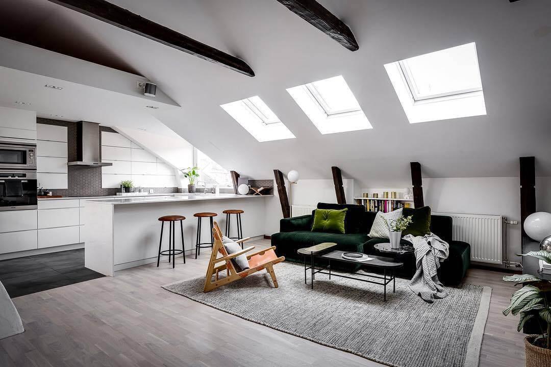 勾配天井でフローリングはライトグレーです。キッチン部分のタイルはダークグレーです。ラグマットも明るい色を使っています。
