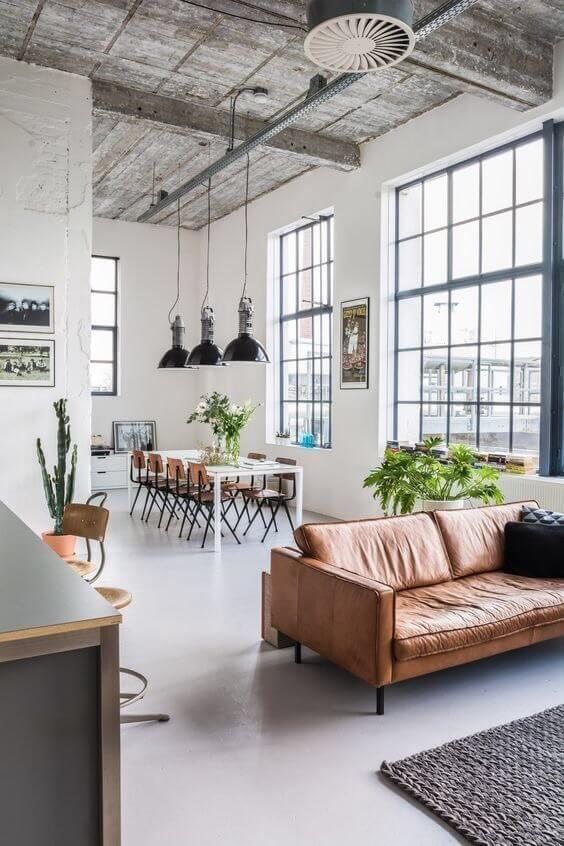 天井が非常に高い開放感のある空間です。白い床にキャメルレザーを使用したソファーを配置しています。キャメルは木目の色と似ているのでダイニングチェアでミディアムブラウンからの木目を使うと統一感を演出することができます。壁と同じ色のダイニングテーブルなのでテーブルの圧迫感は感じません。
