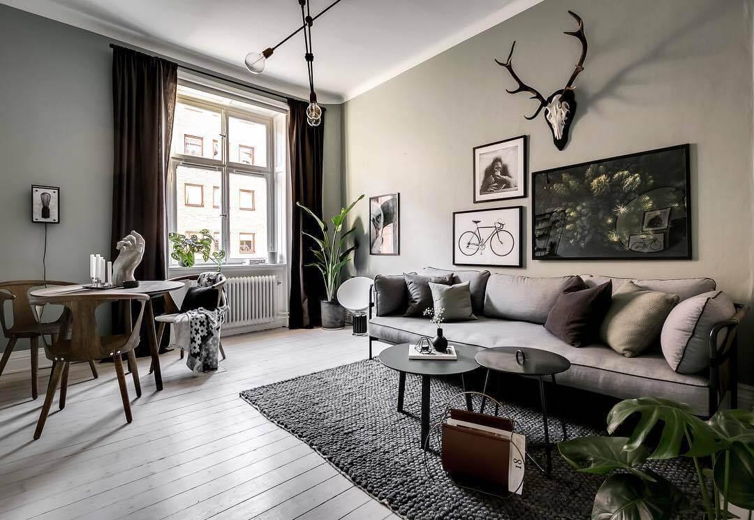 壁面はライムグリーンでソファーはライトグレーですリビングテーブルは丸くて黒いテーブルです。大きいテーブルと小さいテーブルを2つ使ってコーディネートしています。