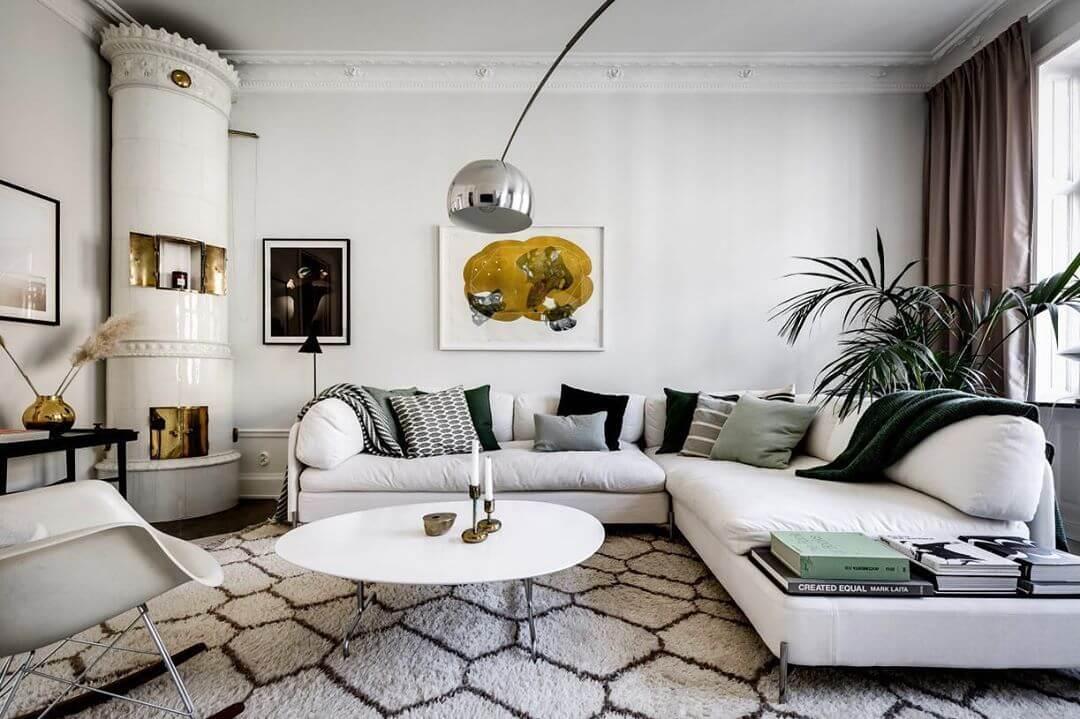 白いソファーとグリーンのクッションでコーディネートしています。部屋の角にあるのは暖炉です。リビングテーブルは変形の白いテーブルを使用しています。
