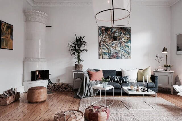 節のあるフローリングはライトブラウンからです。ソファーはダークグレーのソファーでクッションをたくさん置いてアクセントを生み出しています。部屋の角には装飾性のある暖炉があってヨーロピアンアパートのインテリアイメージです。