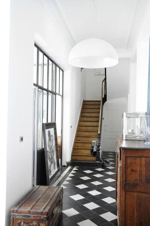 細い通路タイルを敷き詰めて演出しています。どちらかと言うとイギリスによくあるスタイルです。白と黒のタイルを使用しており階段はミディアムブラウンカラーです。家具はアンティーク調でミディアムブラウンカラーで統一しています。