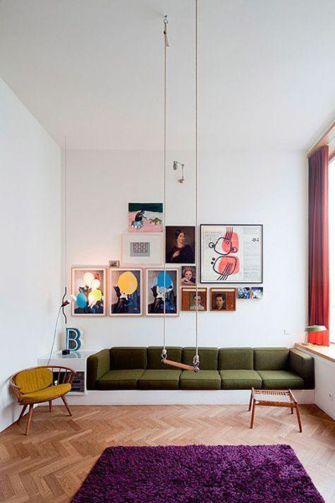 フローリングの色はミディアムブラウンからです。ソファー部分はモスグリーンで天井からブランコが垂れ下がっています。ラグマットはパープルを使用しておりかなりカラフルな印象です。