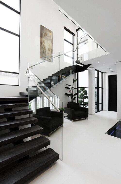 白いタイルの床に黒いソファーと黒い階段です。手すりがガラスで近未来的な印象です。吹き抜けから明るい光がたくさん入っているので黒いソファーが圧迫感を全く感じないです。背の高い観葉植物を置くことで空間の高さがより強調されています。