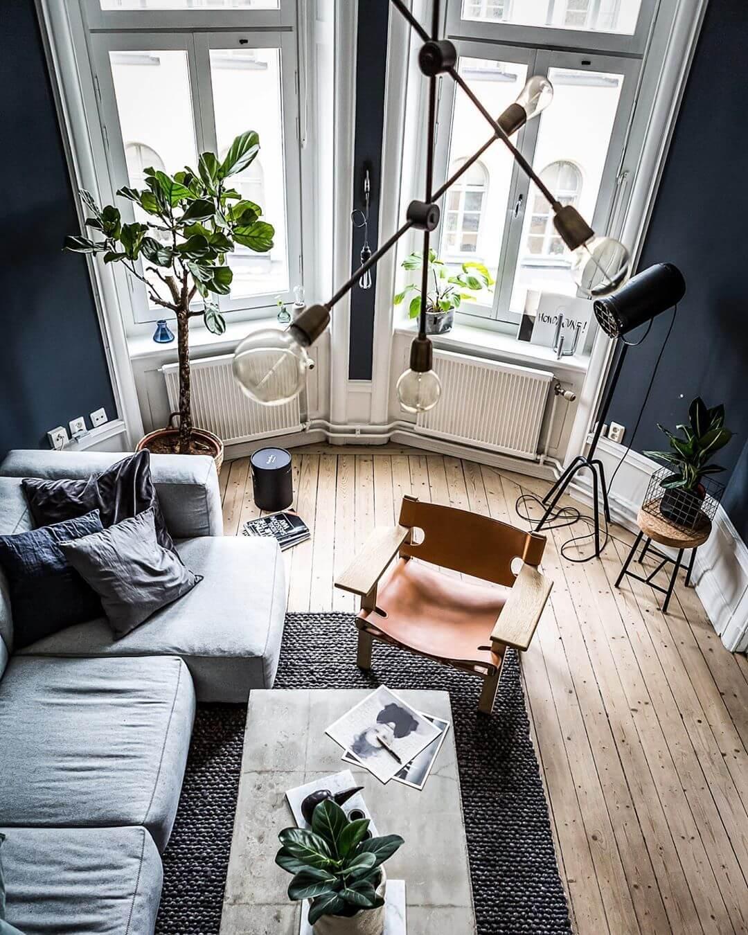 壁面の色はブルーです。クッションの色もブルーにして合わせています。ソファーはカウチタイプでライトグレーを使用しています。リビングテーブルは大理石を使っています。