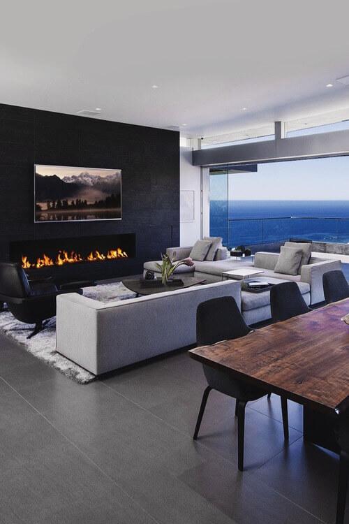 グレーで艶のないタイルを敷き詰めています。暖炉のある壁面はブラックでソファーはライトグレーです。グレーカラーを濃淡を使い分けながら配分しています。色使いとしてはシンプルな色使いです。大きな窓で景色が綺麗な場合は家具で主張する必要はなくシンプルに押さえておくことが良いと思われます。