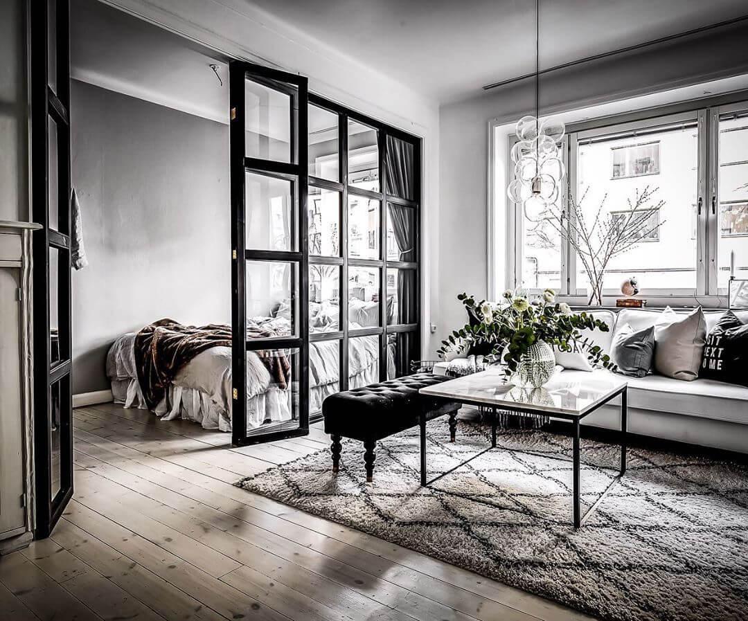リビングルームとベッドルームがガラス張りでつながっている空間です。お部屋をコーディネートするときは全体の統一感が重要です。ホワイトのソファーと大理石のリビングテーブルを使用しています。