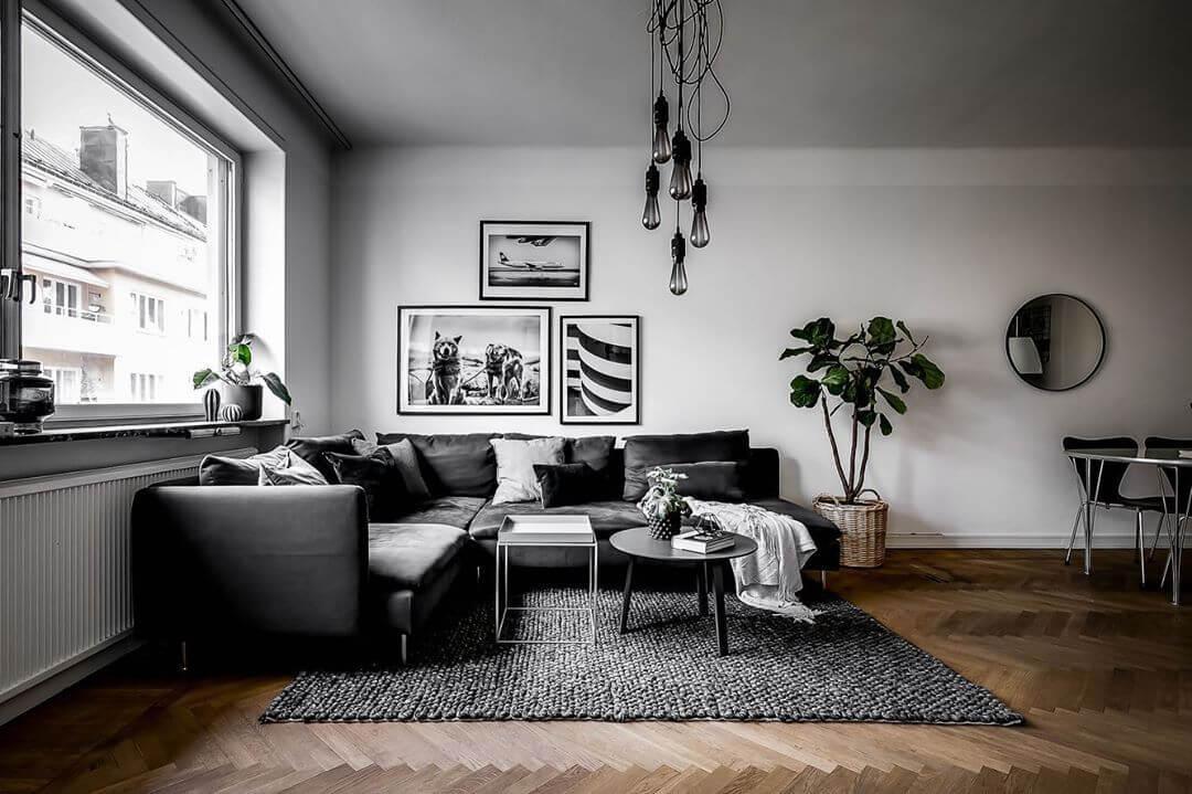 白い壁とヘリンボーンの床です。ソファーはブラックでラグマットはダークグレーです。壁に飾っている絵はモノトーンで統一されています。