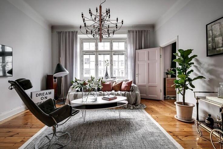 白い壁に節があるフローリングです。ソファーの上にクッションをたくさん置いていますね。海外インテリアではよくある光景です。
