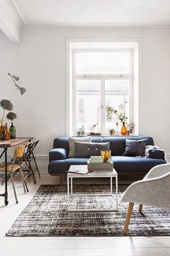 白い壁と窓を背もたれにしながらソファーを置いています。ネイビーのソファーはクールになりやすいですが木材の足を使用しているのでモダンインテリアに偏っているわけではありません。