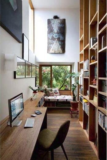 かなり細い空間ですね。おそらく詳細だと思われますが壁面を書棚で埋めています。色を統一することでまとまりを演出しています。窓のサッシが木目になっているのは海外インテリアならではですね。