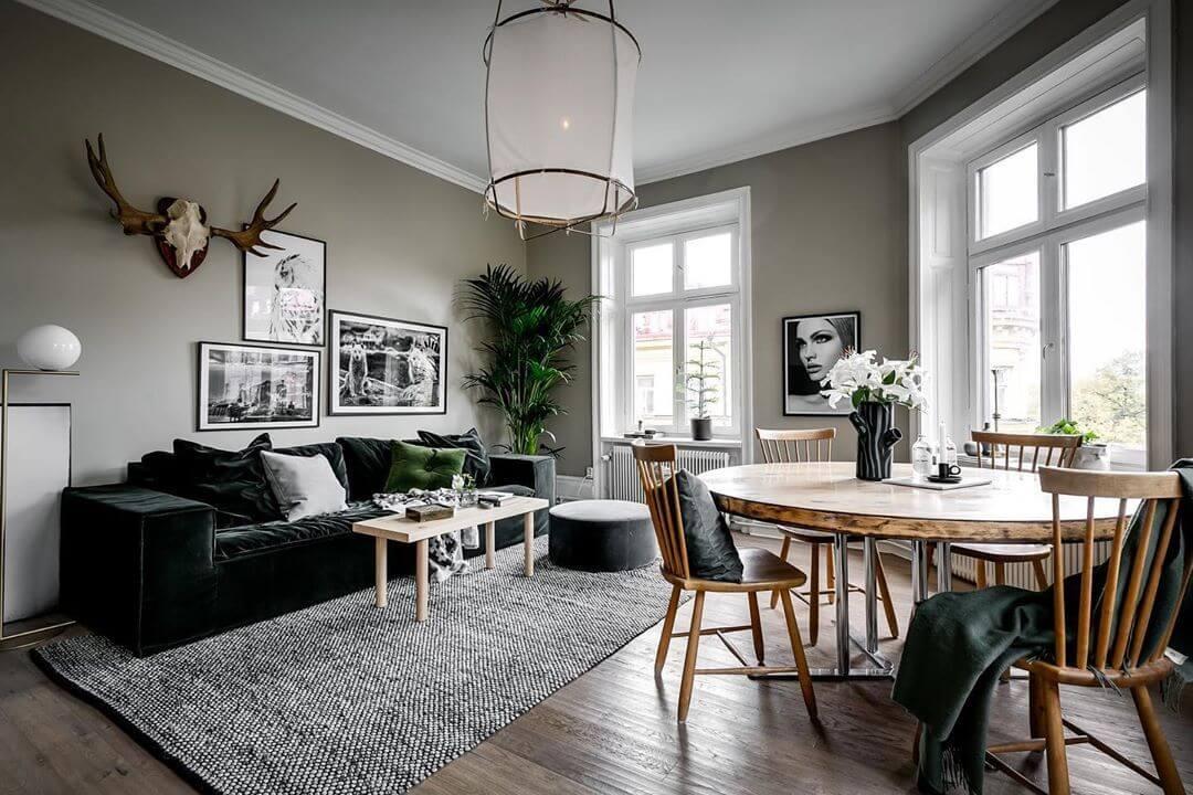壁面がグリーンでソファーがダークグリーンでラグマットはライトグレーです。古材を使った。テーブルを使っています。