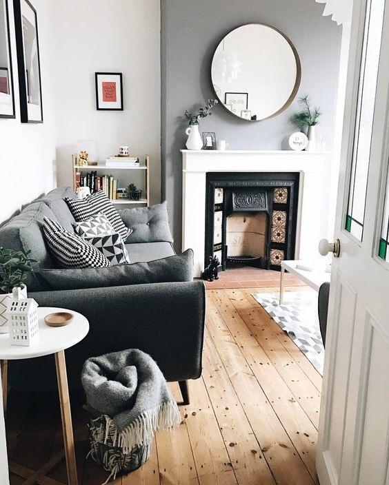 明るめのライトブラウンカラーでフローリングが敷いてあります。あまり広い空間ではありませんがホワイトのテーブルと暖炉が圧迫感を軽減しています。ソファーはグレーからです。クッションも同系色でまとめていてきれいなお部屋です。暖炉の上には丸いミラーが飾ってあります。