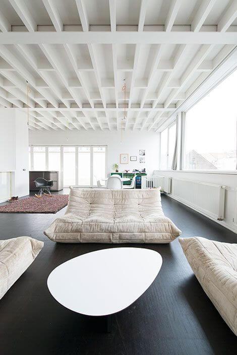 天井の梁が個性的な床の色がブラックの空間にリーンロゼのTOGOを置いたインテリア事例。