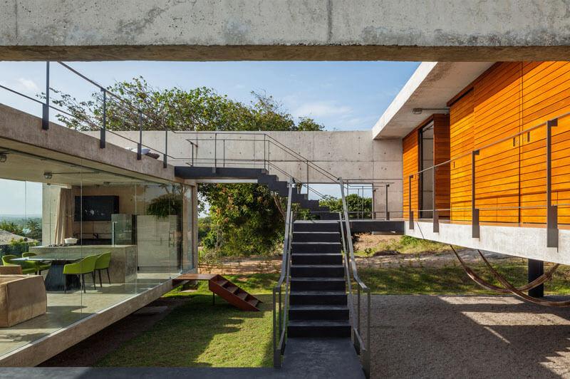 後部のコンクリートブロックは木製の被覆材で柔らかくなります。人間が活動を創造するのに十分な標高が高い。だから、建物の陰になって、2番目の建物の下に空いている宇宙空間は、リラックスできる屋外空間になります。ハンモックと座席が設置されています。