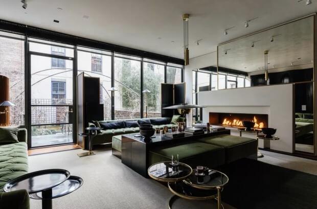 床が白くてソファがグリーン。暖炉の上にミラーで戒能感を演出している海外事例