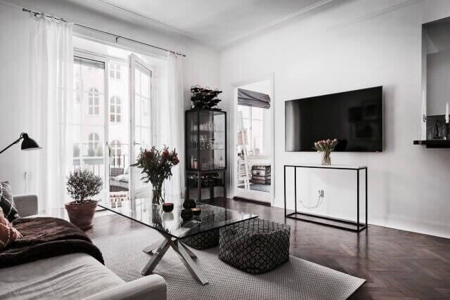 ヘリンボーンの床の色がかなり濃い色でテレビは壁掛けテレビを使用しています。海外のインテリアのアパートの1室の事例。