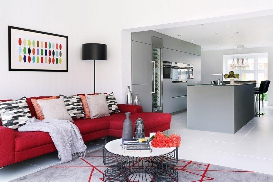 白いタイルの床に赤いカウチ型のソファーを配置しています。フロアランプはブラックです。ラグマットにも赤いラインが入っておりアクセントカラーを赤で設定しています。クッションにも柄を使っており動きを感じさせますね。ただしこのカラーコーディネートはやや秋が来るのが早いと言うデメリットもあります。買い替えのサイクルが長いソファーなどでアクセントカラーにすると飽きてしまったときに変えにくいと言うデメリットがあることも知っておいた方が良いと思われます。