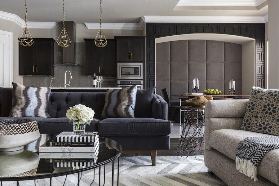 ダークブラウンからのフローリングにベージュ系のソファーとネイビー系のソファーを得る事形で置いています。リビングテーブルはブラックガラスの丸テーブルで足はかなり細いデザインです。キッチンの上の照明は3つるしてありゴールドを使用しています。