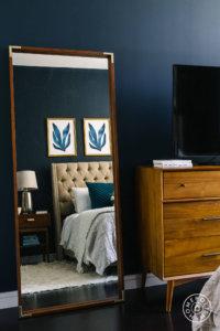 紺色の壁面に姿見を立てかけているイメージ