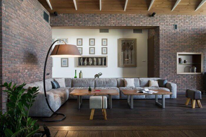 フローリングの色はダークブラウンからでソファーはライトグレーでコーナー形で配置されています。壁面はレンガでどちらかと言うとマットの仕上げです。
