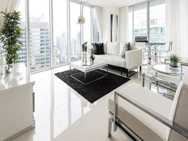 艶のある白いタイルに白いソファー対照的に黒いラグをしてコントラストを生み出しています。かなり高いマンションみたいで景色が非常に綺麗です。