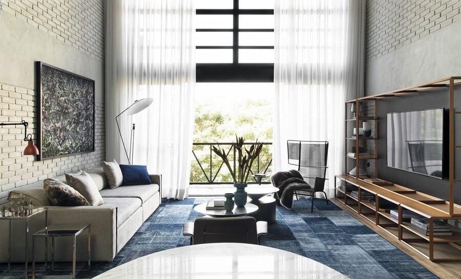 明るいフローリングにベージュ系のソファーでラグマットが非常に大きくしてあります。ラグマットはブルーで部屋全体のアクセントとして機能しています。インダストリアルな内装なので少し冷たい印象がありますが男性的なかっこいい空間でもあります。