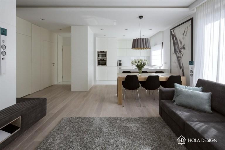 現代的なスタイルの小さなアパートの配置は、白い色の壊れた色合いに基づいていました。秩序だった光が満たされた空間は、内部に味を与えた印象的な要素で変化しました。ダイニングテーブルの上に掛けベニヤオークランプは、アルゼンチンからの要求、オーク材のテーブルの上に持ってきて、インテリアデザインの著者によって推奨白い家具大工を作りました。
