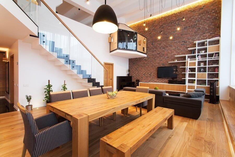 ライトブラウンからのダイニングテーブルとベンチです。床と色が合っていますね。テレビボードの背面の壁面が使い込まれたレンガで少しヴィンテージ感があります。天井がかなり高く吹き抜けになっているので開放感が素晴らしいです。本棚も変わったデザインですね。
